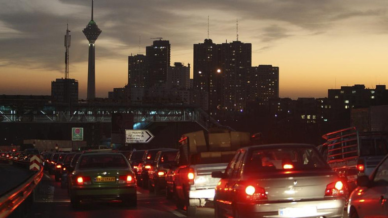 FILE -- In this Saturday, Nov. 27, 2010 file photo, Milad telecommunications tower and residential towers are seen, as cars drive in an evening traffic jam in Tehran, Iran. The nuclear deal struck by Iran and world powers will provide some relief from sanctions for Iran's automakers. The sanctions relief, due to start in early January, 2014, allows French carmakers PSA Peugeot Citroen and Renault to resume shipping auto parts to Iran for assembly by Iran's biggest carmakers Iran Khodro and SAIPA. (AP Photo/Vahid Salemi, File)
