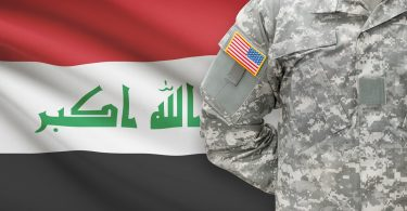 American soldier in front of Iraq flag
