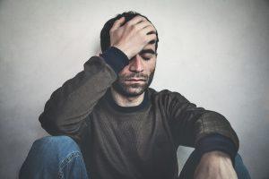 Man Holding Head in Distress
